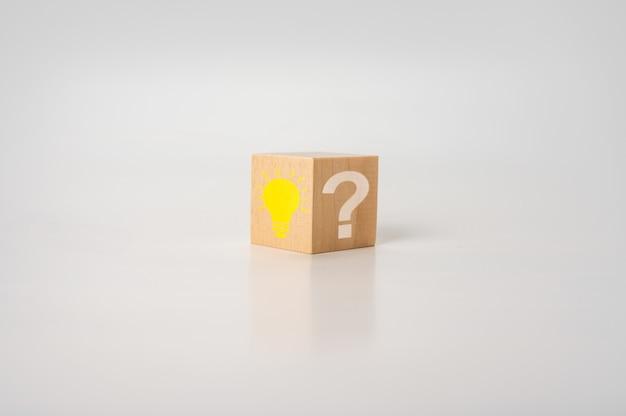 白いテーブルに明るい電球と疑問符が付いた木製の立方体。創造的なアイデア、イノベーション、ソリューションのコンセプト。電球のアイコンと疑問符の記号が付いた木製の立方体。