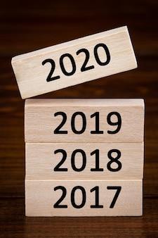 2019年から2020年の単語をめくるブロック付き木製キューブ。解像度、戦略、ソリューション、目標、ビジネス、新年新年、幸せな休日の概念