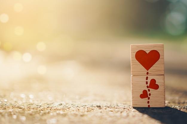 ハートのサインアイコンが付いた木製の立方体と、背景にテキストを配置できるスペース自然の日光をコピーします。バレンタイン愛の季節のコンセプト。