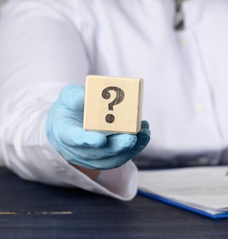 Wooden cube with a question mark in the doctor's hand on a blue surface
