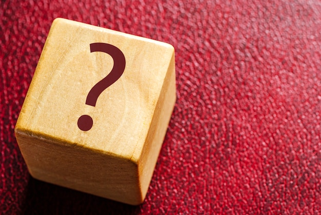 Wooden cube with question mark on red leather