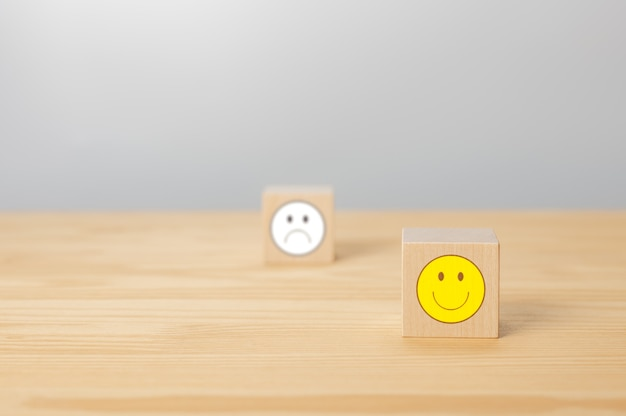 Wooden cube with smile icon face sign cube with sign of negative face icon is blurred in gray