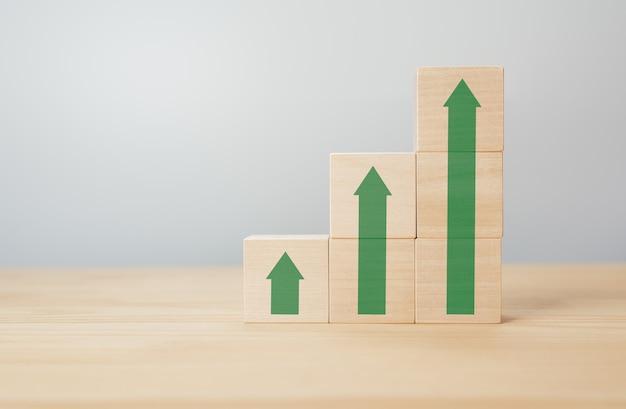 灰色の背景にup緑の矢印と木製の立方体。金融、株式、金利の概念。スタッキングウッドブロック棒グラフ。経済的、経済的またはキャリアの成長、発展。コピースペース
