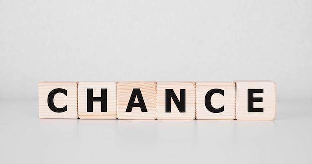 Деревянный куб со словом шанс на фоне стола