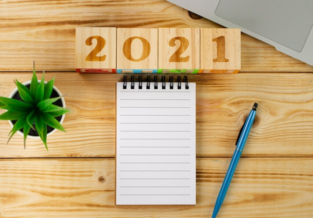 Деревянные кубики 2021 и пустой блокнот на столе