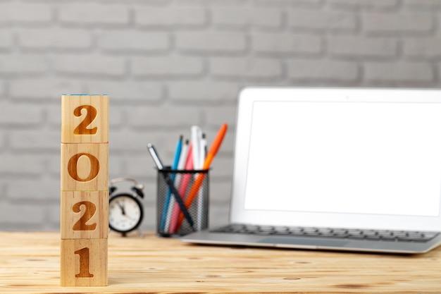 Деревянные кубики 2021 года на рабочем столе с открытым ноутбуком. концепция 2021 года