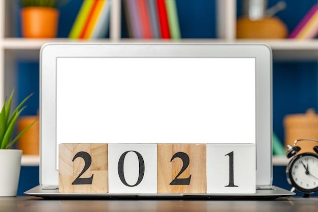 Деревянные кубики 2021 года на рабочем столе с открытым ноутбуком
