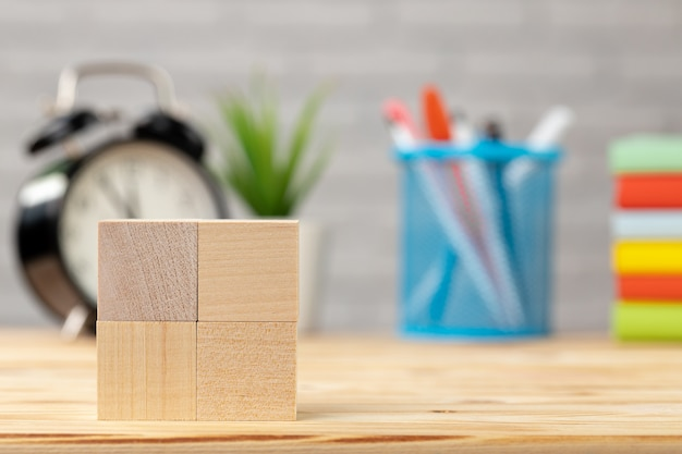 Wooden cubes and alarm clock on desk