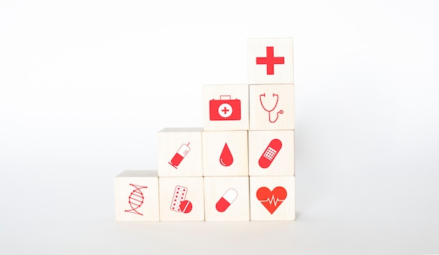 Wooden cubes are icons of icons with honey, analyses, syringe, tablets, pill, band-aid and heart. close up.