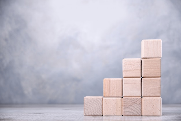 Wooden cubes are stacked in the form of stairs on a wooden table. the concept of development,growth, the boss, the best.