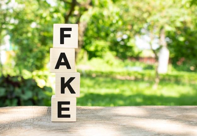 나무 큐브는 정원에 있는 나무 테이블에 수직으로 쌓여 있습니다. fake라는 단어는 검은 글자로 쓰여 있습니다.