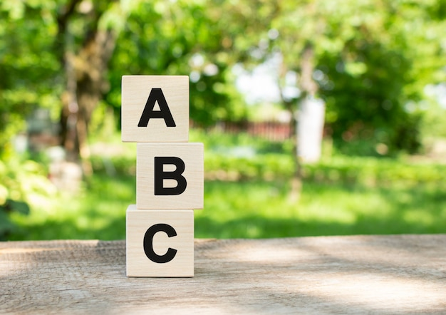 Wooden cubes are stacked vertically on a wooden table in the garden. the word abc is written in black letters.