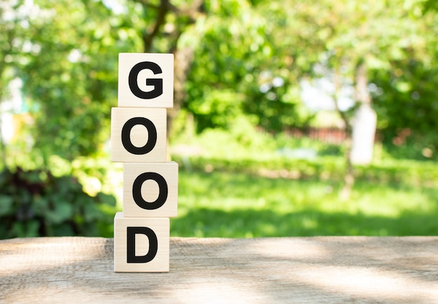 Wooden cubes are stacked vertically on a wooden table in the garden. the word good is written in black letters.