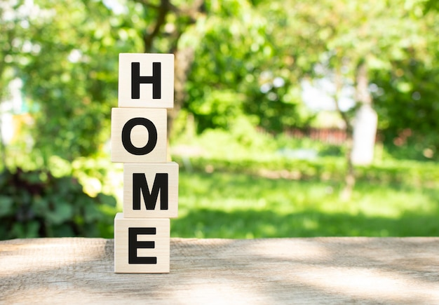 Wooden cubes are stacked vertically on a wooden table in the garden the word home is written in blac...