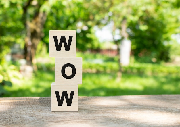 Wooden cubes are stacked vertically on a wooden table in the garden the word wow is written in black...