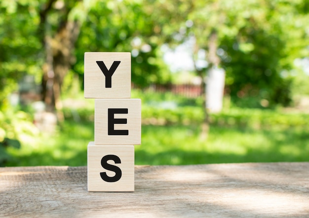 Wooden cubes are stacked vertically on a wooden table in the garden. the word yes is written in black letters.