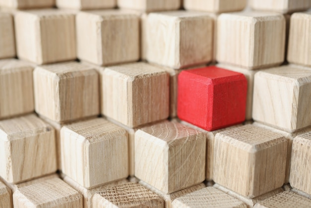 Wooden cubes of beige color in middle of red stands in pyramid individual approach in business