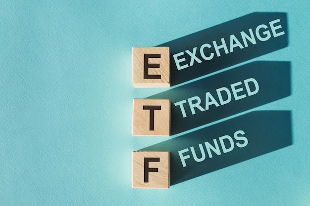 Wooden cubes building word etf on light blue