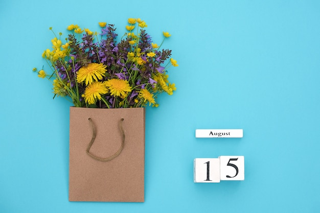 Wooden cubes calendar august 15 and field colorful rustic flowers in craft package on bluen