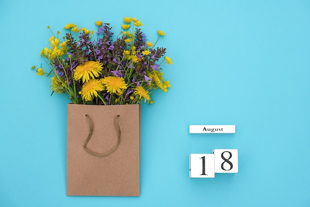 Wooden cubes calendar august 18 and field colorful rustic flowers in craft package on blue background.