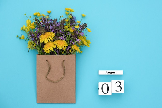 Wooden cubes calendar august 3 and field colorful rustic flowers in craft package ign