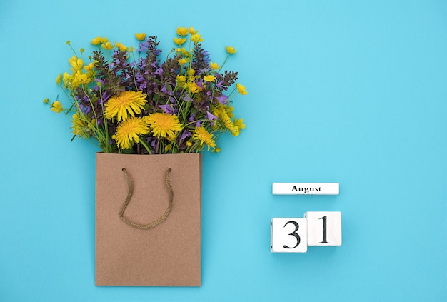 Wooden cubes calendar august 31 and field colorful rustic flowers