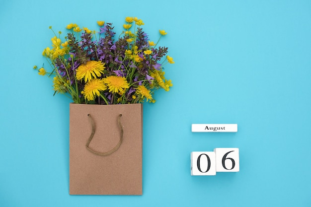 Wooden cubes calendar august 6 and field colorful rustic flowers in craft package on blued design