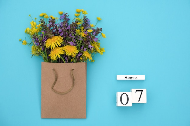Wooden cubes calendar august 7 and field colorful rustic flowers in craft package on bluefor text and design