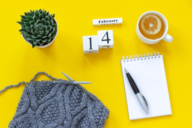 Wooden cubes calendar february 14th. cup of tea with lemon, empty open notepad for text.