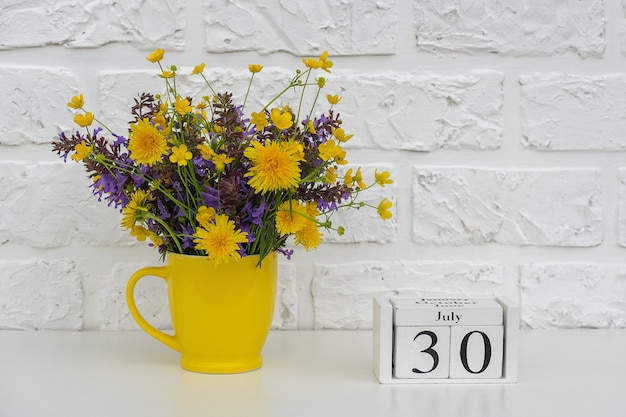 Wooden cubes calendar july 30 and yellow cup with bright colored flowers
