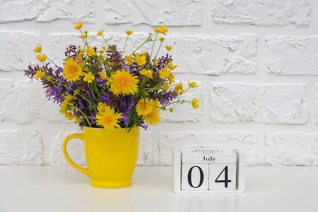 木製キューブカレンダー7月4日と白いレンガの壁に明るい色の花と黄色のカップ。