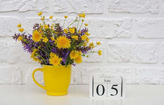 木製キューブカレンダー7月5日と白いレンガの壁に明るい色の花と黄色のカップ。