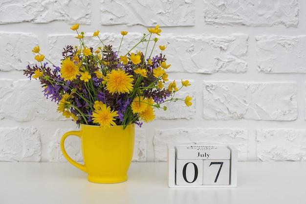 木製の立方体のカレンダー7月7日と白いレンガの壁に明るい色の花と黄色のカップ。テンプレートカレンダーの日付