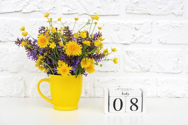 木製の立方体のカレンダー7月8日と白いレンガの壁に明るい色の花と黄色のカップ。