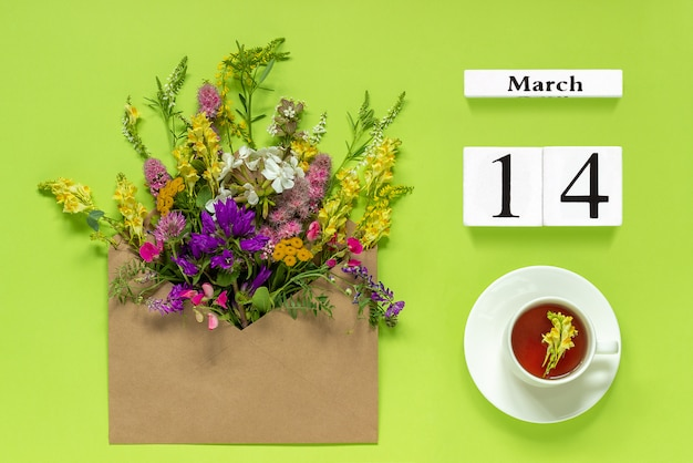 Wooden cubes calendar march 14. cup of tea, kraft envelope with multi colored flowers on green