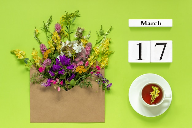 Wooden cubes calendar march 17. cup of herbs tea, kraft envelope with multi colored flowers on green background