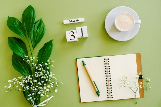 Wooden cubes calendar march 31. notepad, cup of coffee, bouquet flowers on green background. concept hello spring top view flat lay mock up
