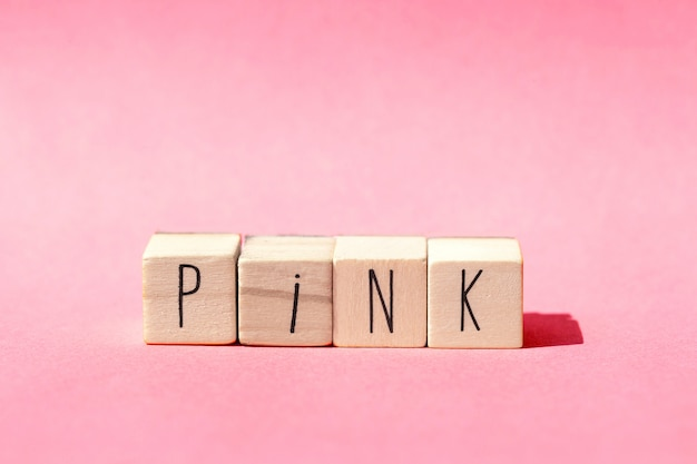 Wooden cubes lie in a row on pink background with the word pink, pastel colored pink natural concept