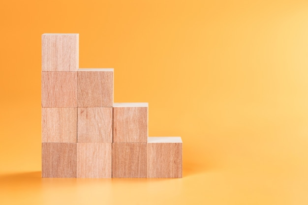 Wooden cubes mock up in stair shape on yellow surface