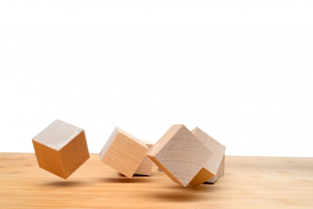 Wooden cubes roll on an inclined plane.