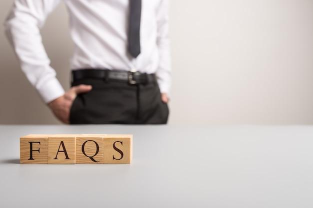 ビジネスマンが立っているfaqを綴る木製の立方体