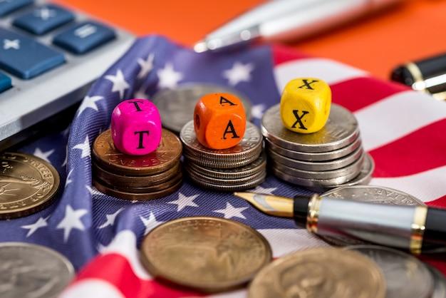 オレンジ色の背景に旗、ドル、コイン、電卓で木製の立方体税