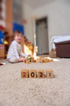 Деревянные кубики с числами 2021 в ряду маленький ребенок строит башню