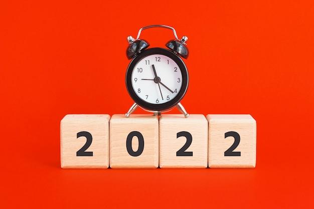 2022年と赤い背景にミニ目覚まし時計と木製の立方体。新年、時間の概念。正方形のブロック。