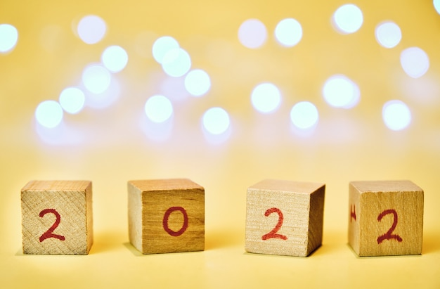Wooden cubes with 2022 written with red numbers on horizontal with yellow background with blue lights out of focus background