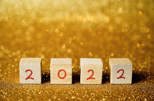 Wooden cubes with 2022 written with red numbers horizontally with shiny gold background