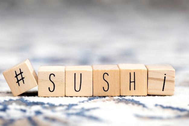 Деревянные кубики с хэштегом и суши слова, социальные медиа и концепция еды