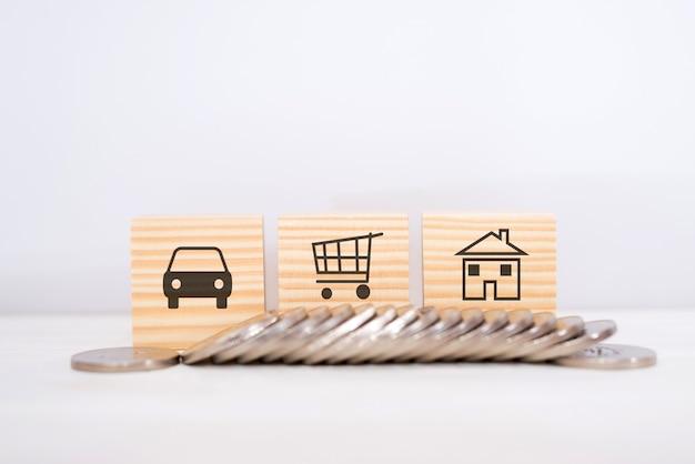 家、自動車、ショッピングカートのシンボルが付いた木製の立方体。コインのスタック。ショッピングのコンセプト。