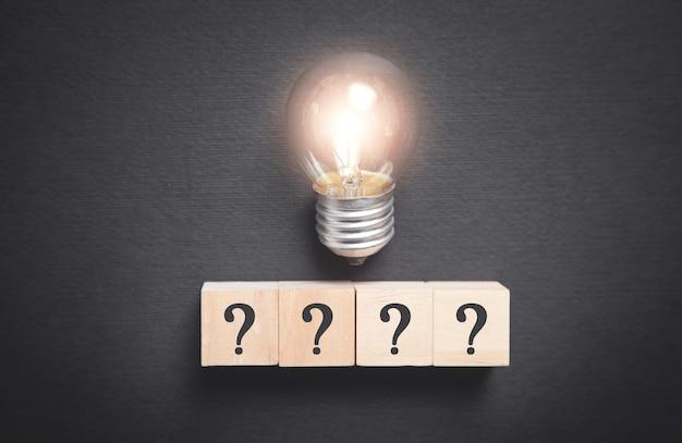 疑問符の記号と電球が付いた木製の立方体。