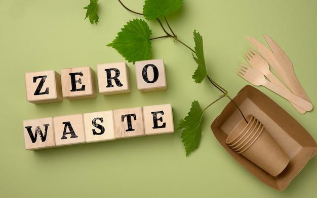Деревянные кубики с надписью ноль макулатуры и тарелки бумажные и одноразовые стаканчики. концепция отказа от пластиковой посуды, сохранение окружающей среды, плоская планировка